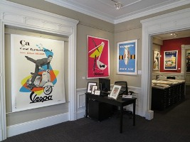 Posters of varied sizes decorate wall of gallery; beige, white, red, blue